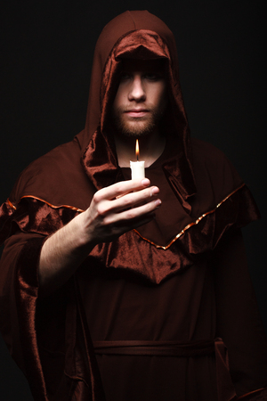 cassock: mysterious Catholic monk  studio shot Stock Photo