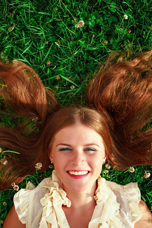 Cute redhead female lying down on fresh green grass photo
