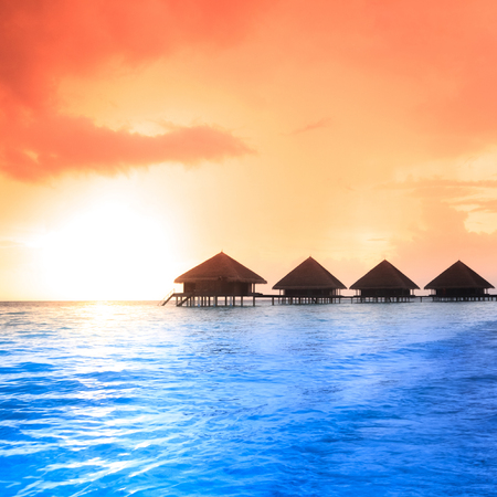 Over water bungalows with steps into amazing green lagoon photo