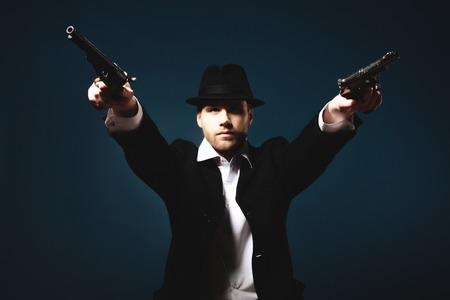 magnum: Photo of man shot with studio lighting, holding a handgun Stock Photo