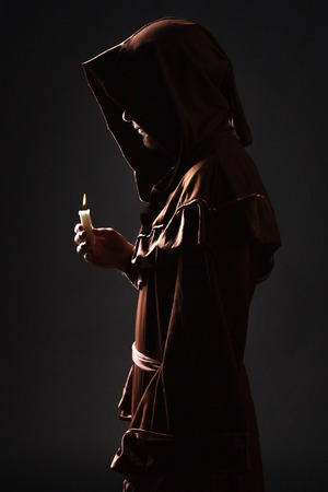 Mystery monk praying on kneels in dark