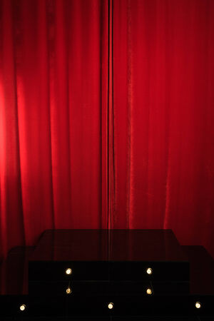 red podium on a of red drape curtains.