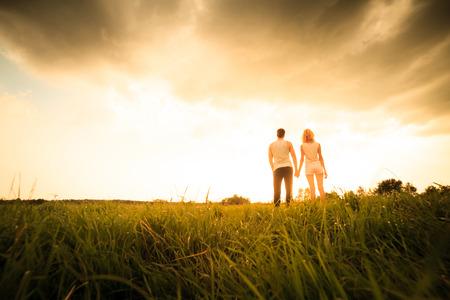 field and sky: pareja caminando por el campo y en la mano el atardecer Foto de archivo