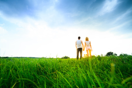walk away: couple walking through the field and holding hands over sunset