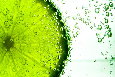 lime green: Green lime with water splash isolated on white background Stock Photo