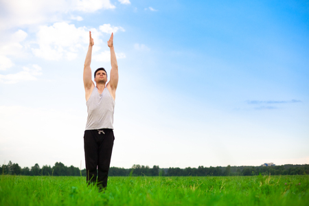 Young man doing yoga in park. Healthy lifestyle. photo
