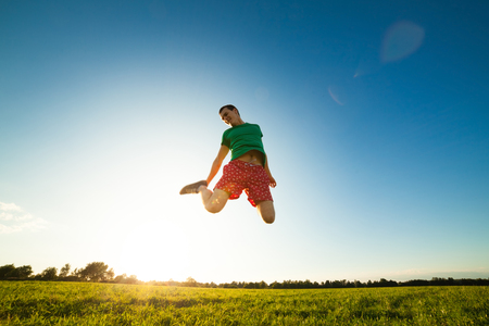 Young man jumping on meadow with dandelions on cloudy background photo