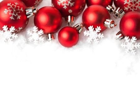 rot: rote Weihnachtskugeln im Schnee auf Weiß. Studioaufnahme
