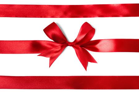 moños navideños: Brillante cinta de raso rojo sobre fondo blanco. tiro del estudio