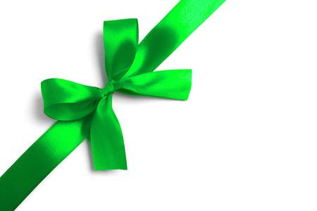 白い背景に光沢のある緑のサテンのリボン。スタジオ撮影