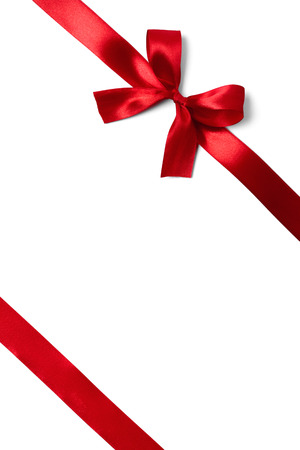 光沢のある白い背景に赤いサテンのリボン。スタジオ撮影 写真素材