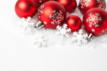 red christmas balls in the snow on white. studio shot