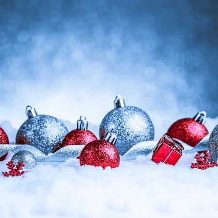 christmas ornament in snow on glitter background. studio shot photo