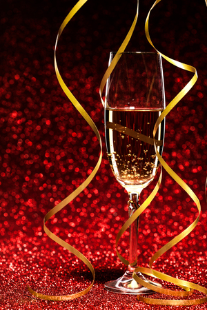 objects drink: glass of champagne with yellow holidays ribbons, on red background