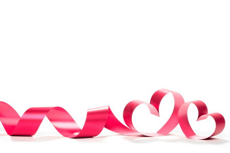 Ribbons shaped as hearts on white photo