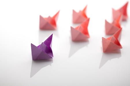 Leadership concept using paper ship among white