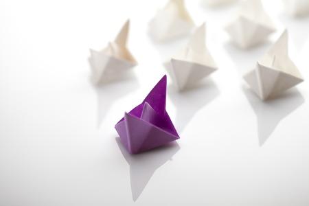 liderazgo: Concepto de la dirección utilizando azul barco de papel entre los blancos