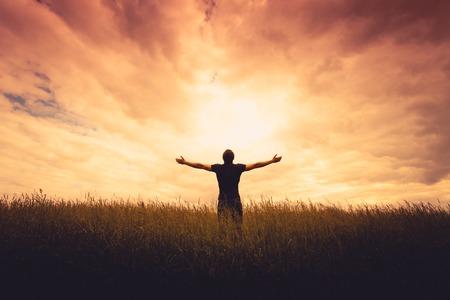 el cielo: silueta del hombre de pie en un campo al atardecer