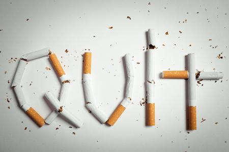 humo: Cigarrillos rotos dispuestos como palabra quit - concepto de dejar de fumar
