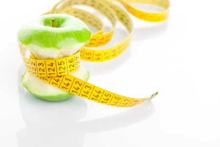 apple core: Green apple core and measuring tape. Diet concept Stock Photo