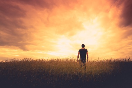 silhouette of man standing in a field at sunset Stock Photo