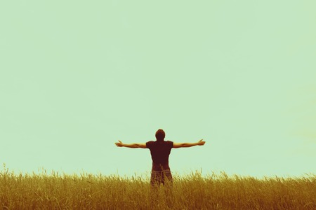lonely man: Silhouette of young man standing with hands open wide