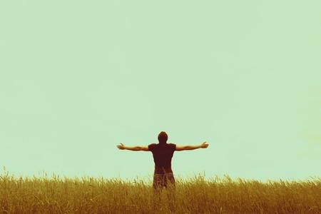 hombre solitario: Silueta del hombre joven de pie con las manos abiertas