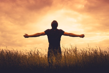 the religion: silhouette of man standing in a field at sunset Stock Photo