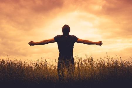manos levantadas al cielo: silueta del hombre de pie en un campo al atardecer