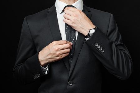 traje formal: hombre de traje sobre un fondo negro. tiro del estudio Foto de archivo