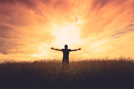 alabanza: silueta del hombre de pie en un campo al atardecer