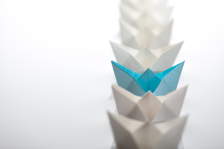 Leadership concept using paper ship among white
