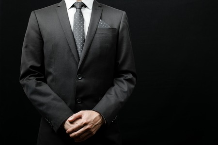 chaqueta: hombre de traje sobre un fondo negro. tiro del estudio Foto de archivo