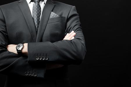 黒の背景にスーツを着た男。スタジオ撮影 写真素材