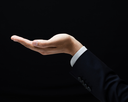 open palm: Open palm hand gesture of male hand on dark background Stock Photo