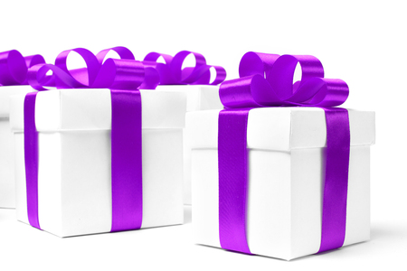 ribbon bow: White gift box with purple ribbon bow and christmas balls around, isolated on white background