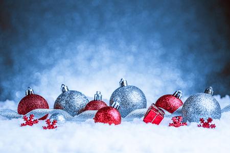 キラキラ背景に雪の中でクリスマスの飾り。スタジオ撮影
