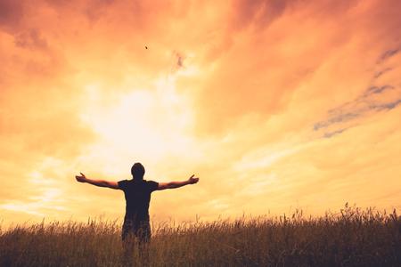 sol radiante: Silueta de hombre y sol sobre fondo de cielo.