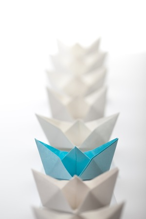 supervise: Leadership concept using paper ship among white