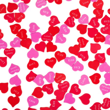 valentine          s day candy: Red and purple hearts with white background. Studio shot