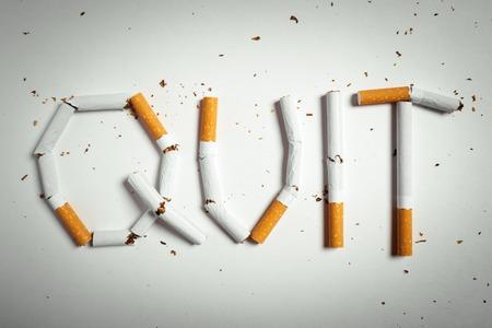 unhealthy living: Broken cigarettes arranged as a word quit - stop smoking concept