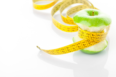 apple core: Green apple core and measuring tape.