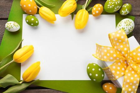 Pasen achtergrond met kleurrijke eieren over wit hout Stockfoto