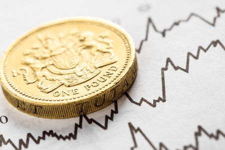 The coin one pound on graphics background. Rate of the pound sterling
