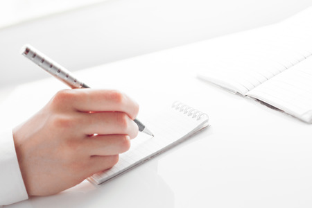 entries: womans hand writing entries in a notebook. studio shot Stock Photo