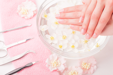 Beautiful womans hands with manicure in bowl of water. Studio shot