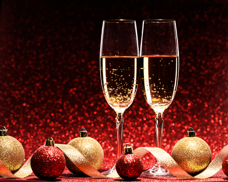 two glasses of champagne ready for christmas celebration, on red background Imagens