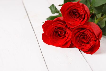 Three red roses lie on white table