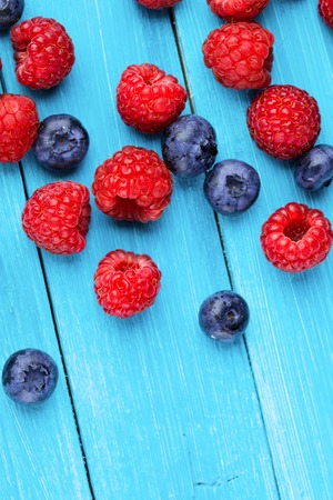 Blueberry and raspberries on blue wooden background