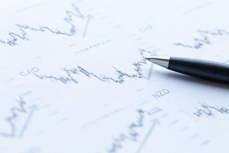 Financial graphs analysis and pen. Studio shot